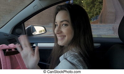 Portrait of Young Beautiful Smiling Student Girl Getting Out of Car And Waving At Camera