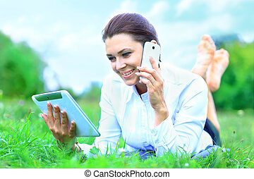 Portrait of young beautiful smiling woman with tablet pc and talking on  mobile phone, outdoors
