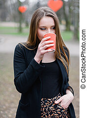 Portrait of young beautiful stylish girl drinking coffee in the park