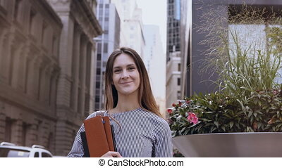 Portrait of young beautiful successful businesswoman near office building in New York, America. Female holds documents.
