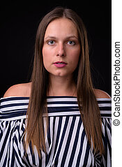 Portrait of young beautiful woman against black background