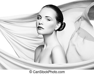 Portrait of young beautiful woman against flying fabric. Beauty woman face closeup. Professional makeup