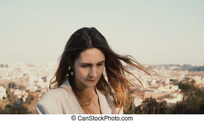Portrait of young beautiful woman against the panorama of Rome, Italy. Dreamy female looking at camera and smiling.