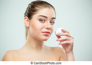 Portrait of young beautiful woman applying moisturizing cream on her face