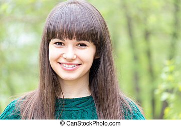 portrait of young beautiful woman brunette girl happy smiling & looking at camera on summer green outdoors background