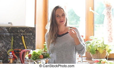 Smiling woman on a diet sitting and looking at camera. A vegetarian girl eating a salad.