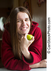 Portrait of young beautiful woman in a red jacket with long hair holding the hands apple.