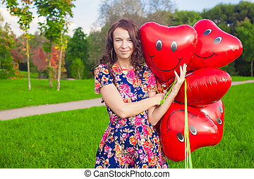 Portrait of young beautiful woman in colorful dress with red balloons