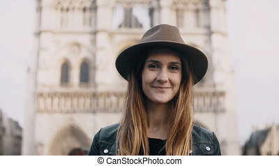 Portrait of young beautiful woman in hat near the Notre Dame in Paris, France. Female looking at camera and smiling.