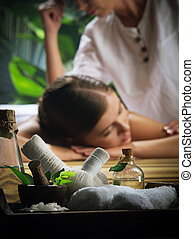 Portrait of young beautiful woman in spa environment. Focused on objects.