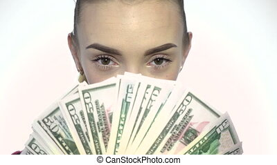 portrait of young beautiful woman iwth a lot of money in hands looking at the camera and winking in studio