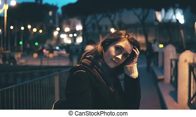 Portrait of young beautiful woman looking at camera and doing up hair. Girl turns, goes away in the evening city.