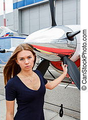 portrait of young beautiful woman near a chrome fairing of a propeller of the business jet