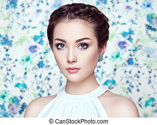 Portrait of young beautiful woman on a background of flowers