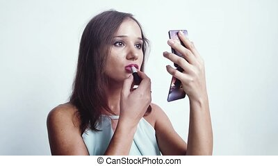 Portrait of young beautiful woman painting lip gloss by sexy...