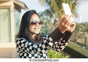 portrait of young beautiful woman wearing sun glasses take a...