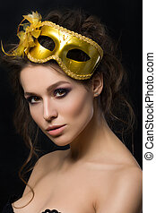 Portrait of young beautiful woman wearing golden party mask