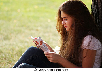 Portrait of young beautiful woman reading magazine