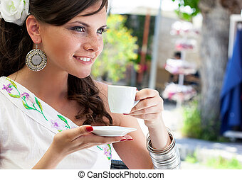 Portrait of young beautiful woman sitting in a cafe outdoor drinking tea