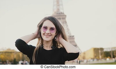 Portrait of young beautiful woman standing near the Eiffel...