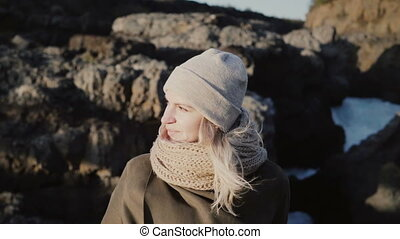 Portrait of young beautiful woman standing near the mountain and looking around, hair waving on wind in sunny day.