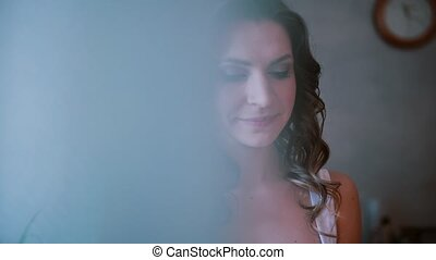 Portrait of young beautiful woman standing near the window. Girl smells the cupcake. View through the curtain.