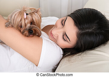 Portrait of young beautiful woman resting with her dog