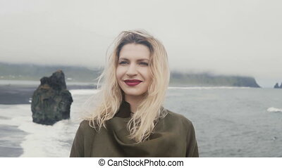 Portrait of young beautiful woman standing on black beach,...