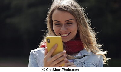 Portrait of young beautiful woman using app on smartphone, smiling and texting on mobile phone. Woman wearing in the red scarf standing in the city park.