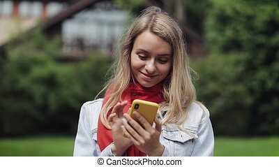 Portrait of young beautiful woman using app on smartphone, smiling and texting on mobile phone. Woman wearing in the red scarf standing near a country house.