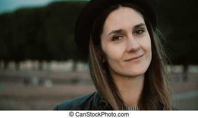 Portrait of young beautiful woman standing in the park and smiling. Happy female in hat looking at camera, hair waving.