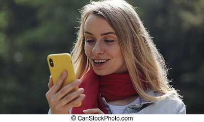 Portrait of young beautiful woman wearing in the red scarf using smartphone, checking phone and celebrating good news in a park. Girl standing in the city park.