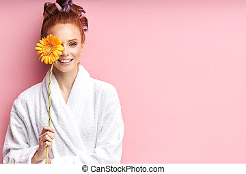 Portrait of young beautiful woman with daisy flower wearing bathrobe, isolated on pink background