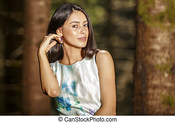 Portrait of young beautiful woman with dress, on green background summer nature.