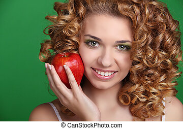 Portrait of young beautiful woman with healthy glossy hair holding red apple
