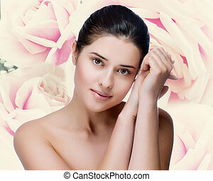 Portrait of young beautiful woman with healthy skin. Roses background