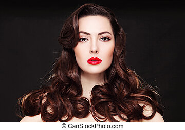 Portrait of young beautiful woman with long curly hair and red lipstick
