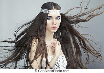 Portrait of young beautiful woman with long flowing hair. Fashio