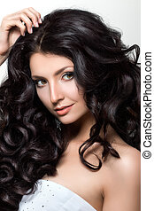 Portrait of young beautiful woman with luxuriant black hair