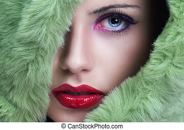 Portrait of young beautiful woman with green fur.