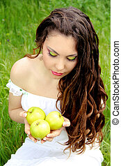 Portrait of young beautiful woman with apples and long curly hair