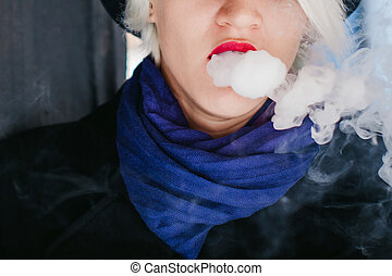 portrait of young beautiful woman with white hair, in a black coat, a skirt and a black hat, smoking an electronic cigarette, blowing the smoke vapor