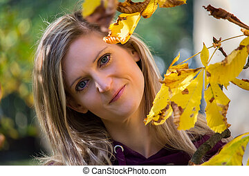 Portrait of young beautiful woman with yellow leaves