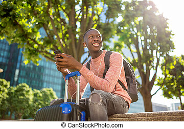 young black man smiling with mobile phone and travel bags