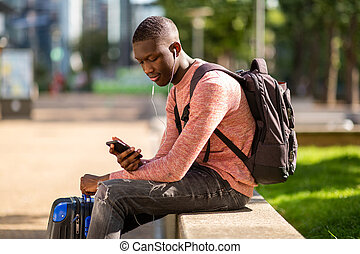 young black travel man sitting outside with mobile phone and bags