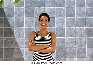 young black woman in striped dress laughing against gray wall