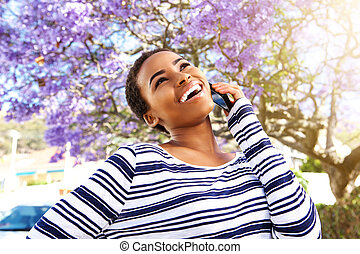 young black woman laughing with cell phone outside