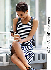 young black woman sitting outside with cup of coffee and mobile phone