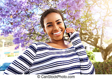 young black woman smiling outside with cell phone