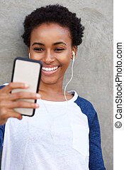 young black woman smiling with mobile phone and earphones